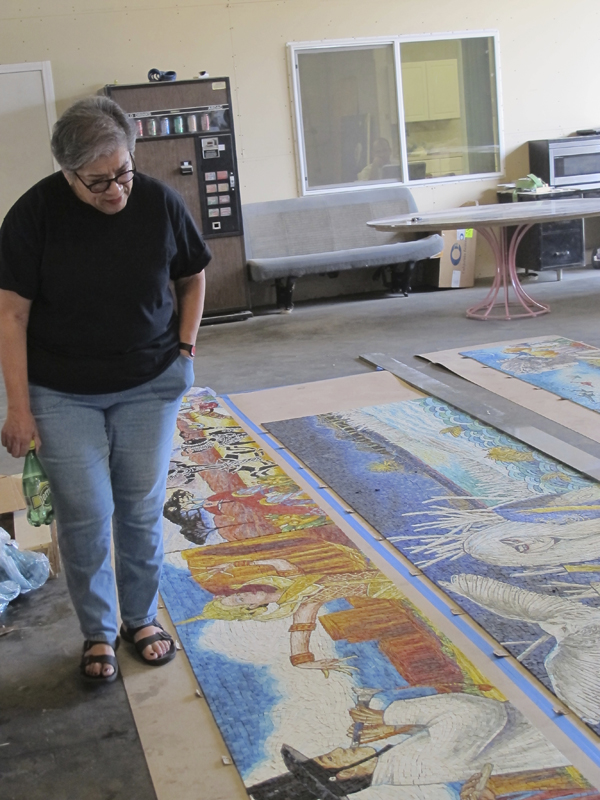 Judithe Hernandez inspecting her artwork panels after they were delivered by artwork fabricator Perdomo Studio to ensure that the colors of her original artwork are accurately reflected, and that the color is consistent among all 24 of the panels.
