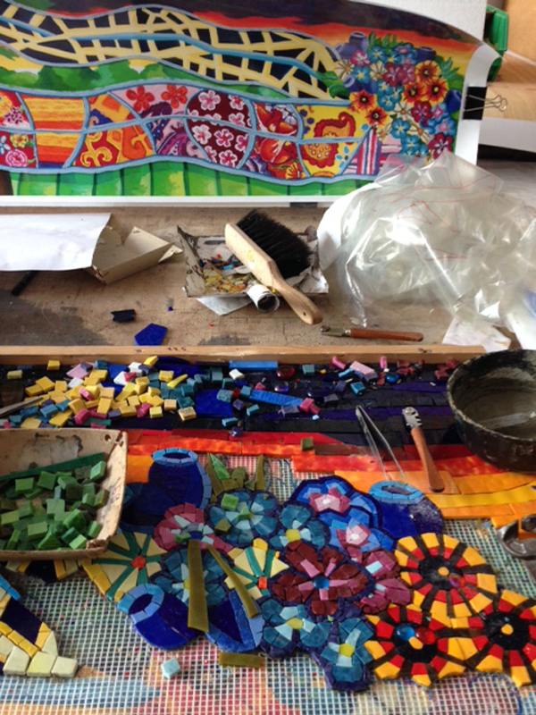 The two photos above show the assembly of thousands of glass mosaic pieces to match the artist's original mixed media paintings at the fabricator's shop. The high resolution scans of the original paintings are visible underneath a mesh base, onto which the mosaic pieces are adhered. Photo courtesy Mayer of Munich.
