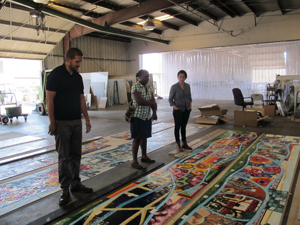 Nzuji de Magalhaes inspecting her artwork with Metro Art staff after they were delivered by the artwork fabricator to ensure that the original artworks are accurately reflected, and that the color is consistent among all eight of the panels.