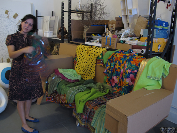 The artist standing with the clothing used as the subject in one of her original photographic artworks for the 17th Street/SMC Station, at her studio during a visit by Metro Art staff.