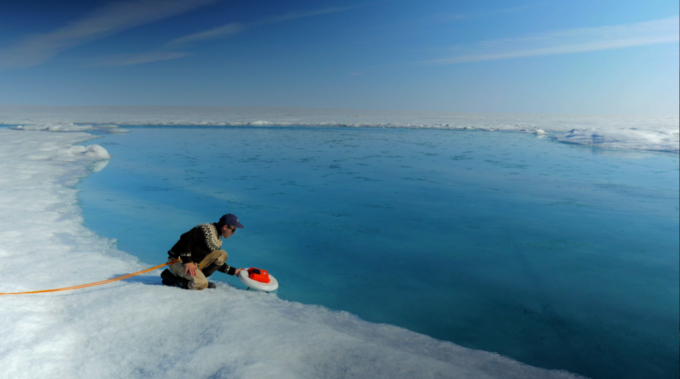 A researcher studies meltwater in Greenland this past summer. Credit: NASA.