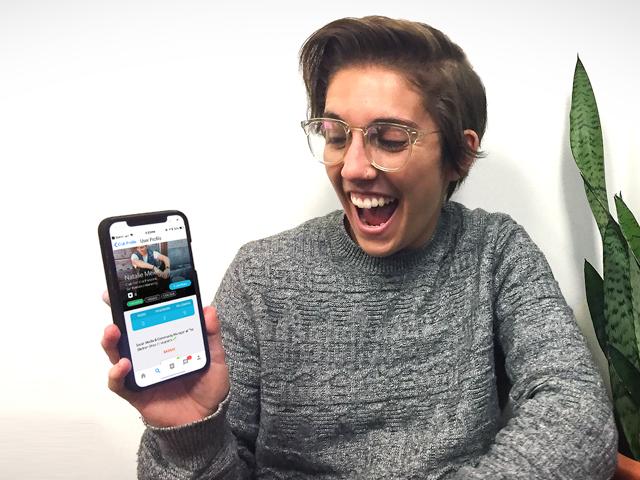 नताली मायर अपने फोन पर  MyLion दिखाते हुए