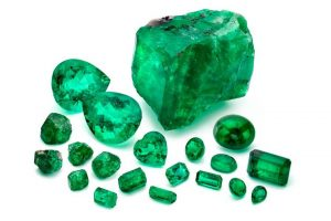 Loose emeralds from Marcial de Gomar Collection. Nine Pillars of Andes rough emeralds shown at the bottom left-hand corner of the image