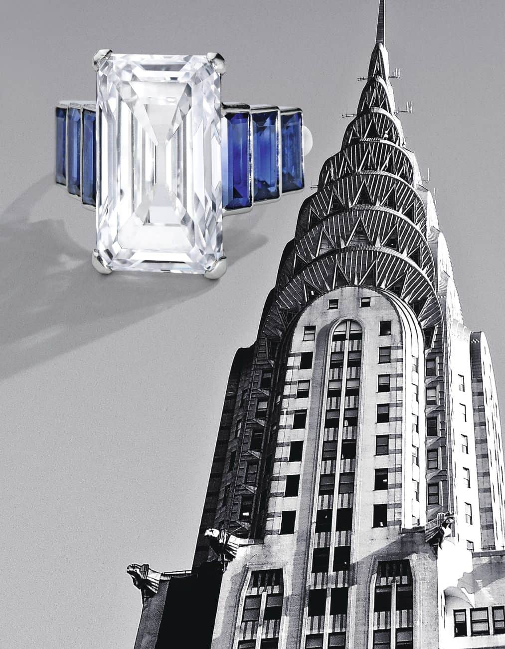 Lot 251 -Art Deco Platinum, Diamond and Sapphire Ring, France, with the ART Deco New York Chrysler Building in the background, both depicting geometric features characteristic of this period