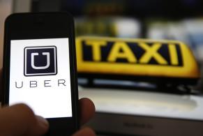 Logo de uber en un smartphone al lado de un cartel de taxi