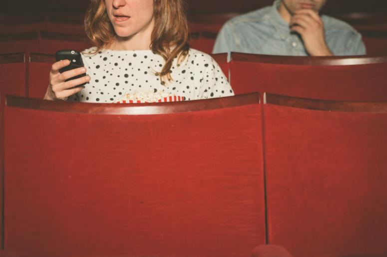 Woman using her cell phone in a theater as a young man sitting behind her looks on.