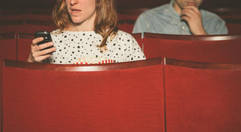 Woman using her cell phone in theater while young man sitting behind her looks on.