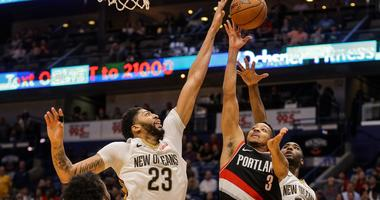 Mar 27, 2018; New Orleans, LA, USA; Portland Trail Blazers guard CJ McCollum (3) shoots over New Orleans Pelicans forward Anthony Davis (23) and forward E'Twaun Moore (55) during the second half at the Smoothie King Center. The Trail Blazers defeated the