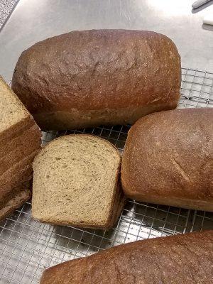 Sliced fresh bread on cooling racks.