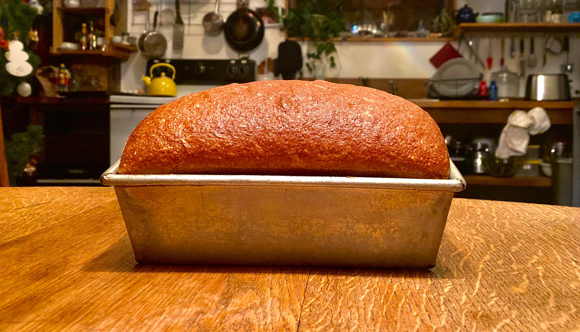 Loaf of bread in pan sitting on table in rustic kitchen