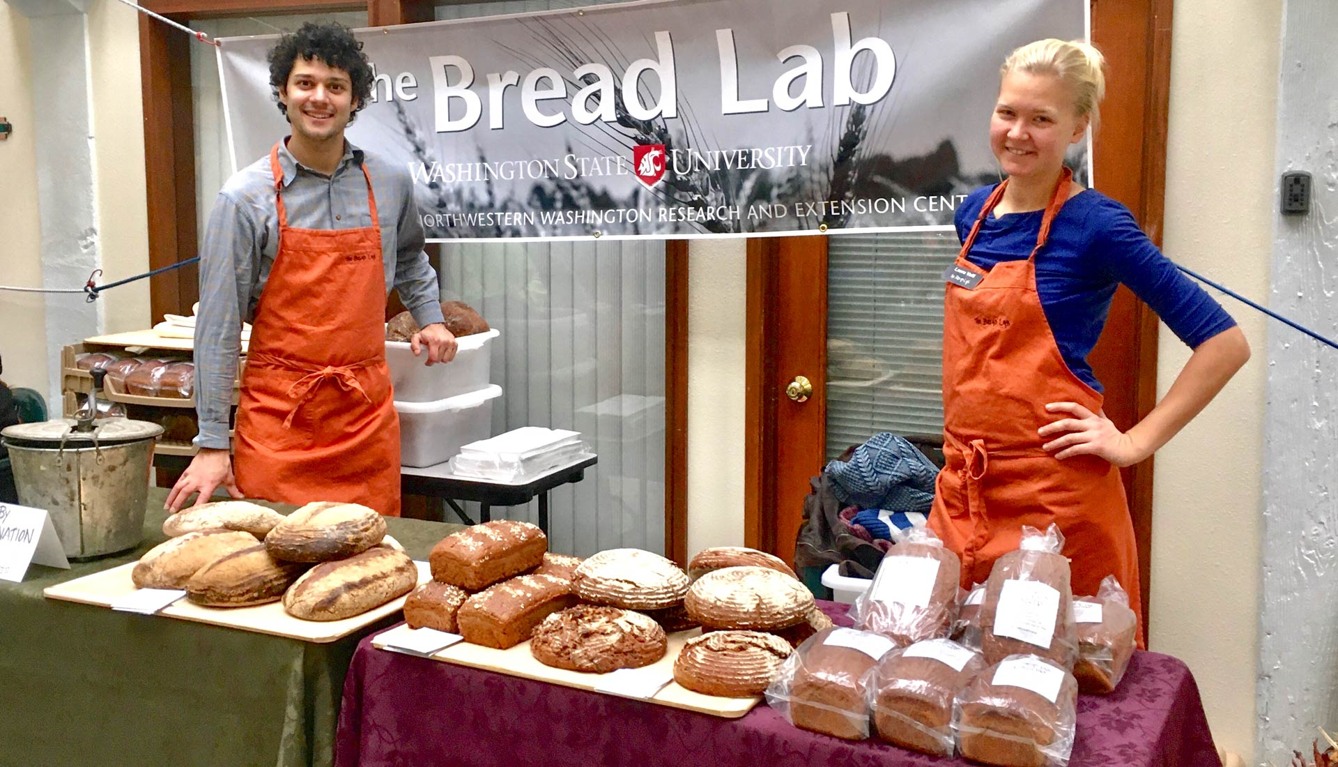 Young man and woman in orange aprons stand at table full of bread.