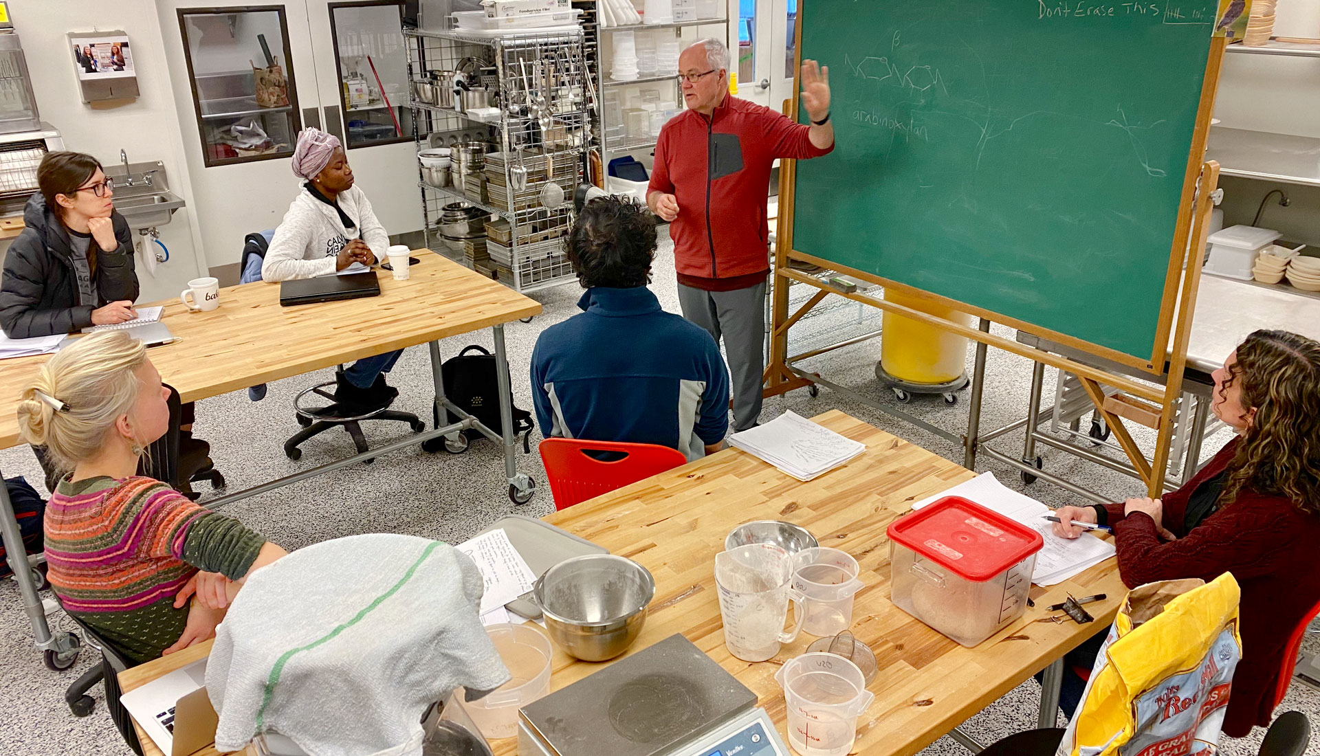 Older man lectures at blackboard to a small group in commercial kitchen