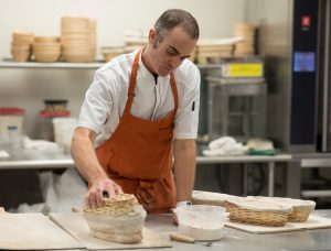 Man in orange apron transfers risen dough from wicker basket onto a peel.