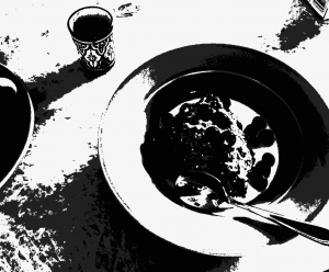[Grainy black and white] bowl of porridge on a table.