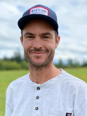 Man with stubble and blue baseball cap.
