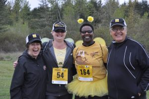 Four people smiling, one dressed as a bee