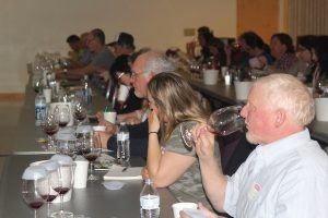 Participants in classroom drink wine samples from glasses.
