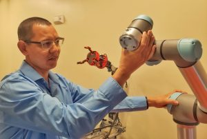 Scientist adjusts robotic components in lab.