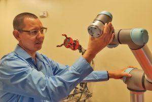 Scientist adjusts robotic components in lab.