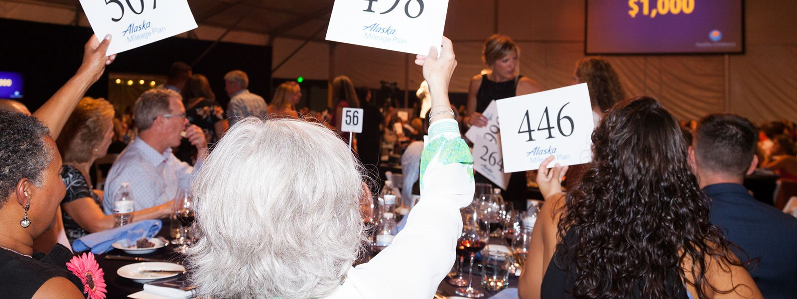 guests hold up bid numbers at a previous Auction of Washington wines gala.