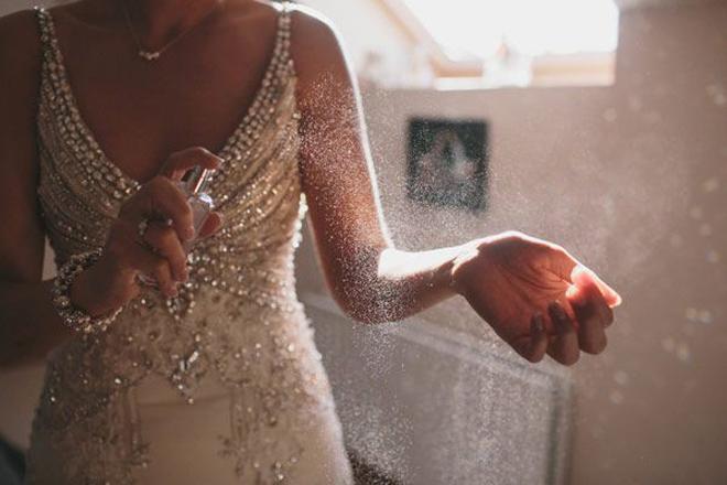 Bride spraying perfume.