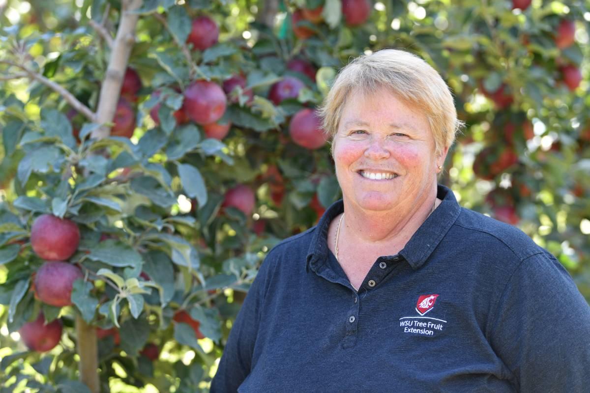 Karen Lewis standing in front of apple orchard.