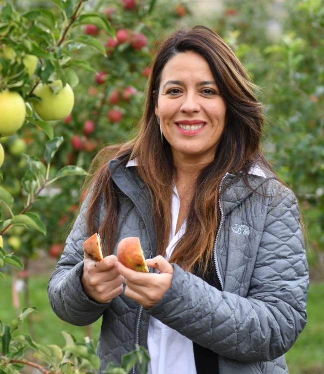 Carolina Torres standing in apple orchard holding cut apple.