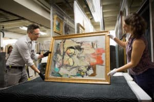 The recovered painting by Willem de Kooning is readied for examination by UA Museum of Art staff Nathan Saxton (r), Exhibitions Specialist, and Kristen Schmidt, Registrar