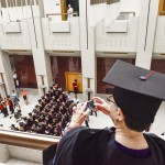 President Cauce takes a photograph from a balcony above a group of Tsinghua University graduates