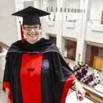 President Cauce, in graduation cap and gown, poses on a balcony