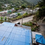 A home with a temporary roof in a sheltered valley of hilly Jayuya.