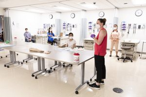 Students in a nursing simulation class spread out around the classroom to follow physical distancing guidelines