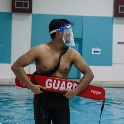 A lifeguard wearing a face shield and holding a rescue buoy laughs in front of the pool.