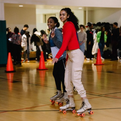 Two students roller skate together in a Rec gym with smiles on their faces.
