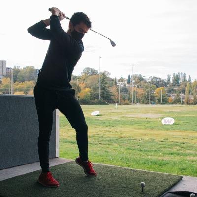 """A student wearing red shoes swings at a golf ball at the Golf Range. Behind him, two signs reads, """"W"""" in purple."""