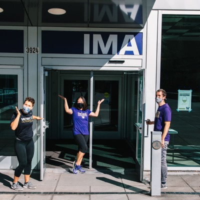 Masked student fitness instructors wave in welcome at the front door of the IMA.
