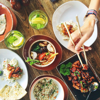 A hand holding chopsticks reaches in to take food from one of several plates of delicious-looking food.