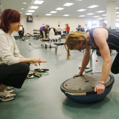 A woman balances her arms on a balance board as her trainer watches her form.
