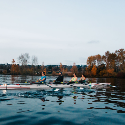 Four rowing participants row in Lake Washington. Behind them the sky is pale blue and the trees have fall leaves on them.