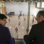 President Cauce and Commissioner Scott watch a Washington Husky Men's Basketball practice