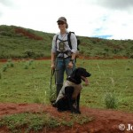 Young woman smiles at camera with a black lab obediently sitting at her feet. Clay soil hills with spars vegetation spread out behind them.