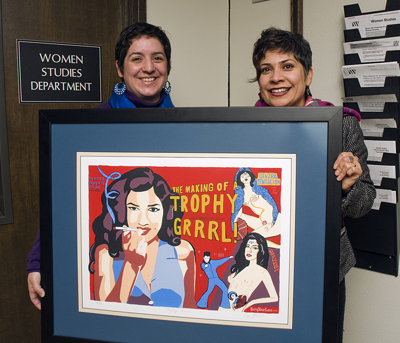 Nicole Robert, left, and Michelle Habell-Pallan hold a reproduction of the cover of Lysa Floses's album, 'The Making of A Trophy Girl.' A Chicana rocker from East Los Angeles, Flores was included in Habell-Pallan's research for the class Gender, Music and Nation. | Photo by Mary Levin