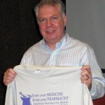 State senator Ed Murray holds up a UW School of Pharmacy T-shirt students gave to him during a tour of their school.