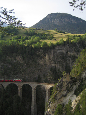 A train crosses a river gorge in the Swiss Alps that drops steeply from the floor of the broad glacial valley above it. (Credit: Oliver Korup)