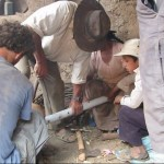 EWB members install pipes to bring potable water to homes.