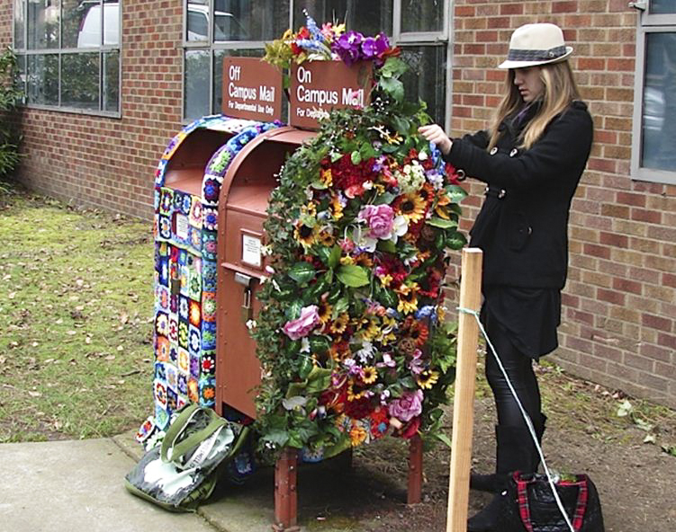 Madelyn Hagen works on the flower mailbox; next to it is the granny afghan mailbox. | Photo by Marco Solis-Bethancourt
