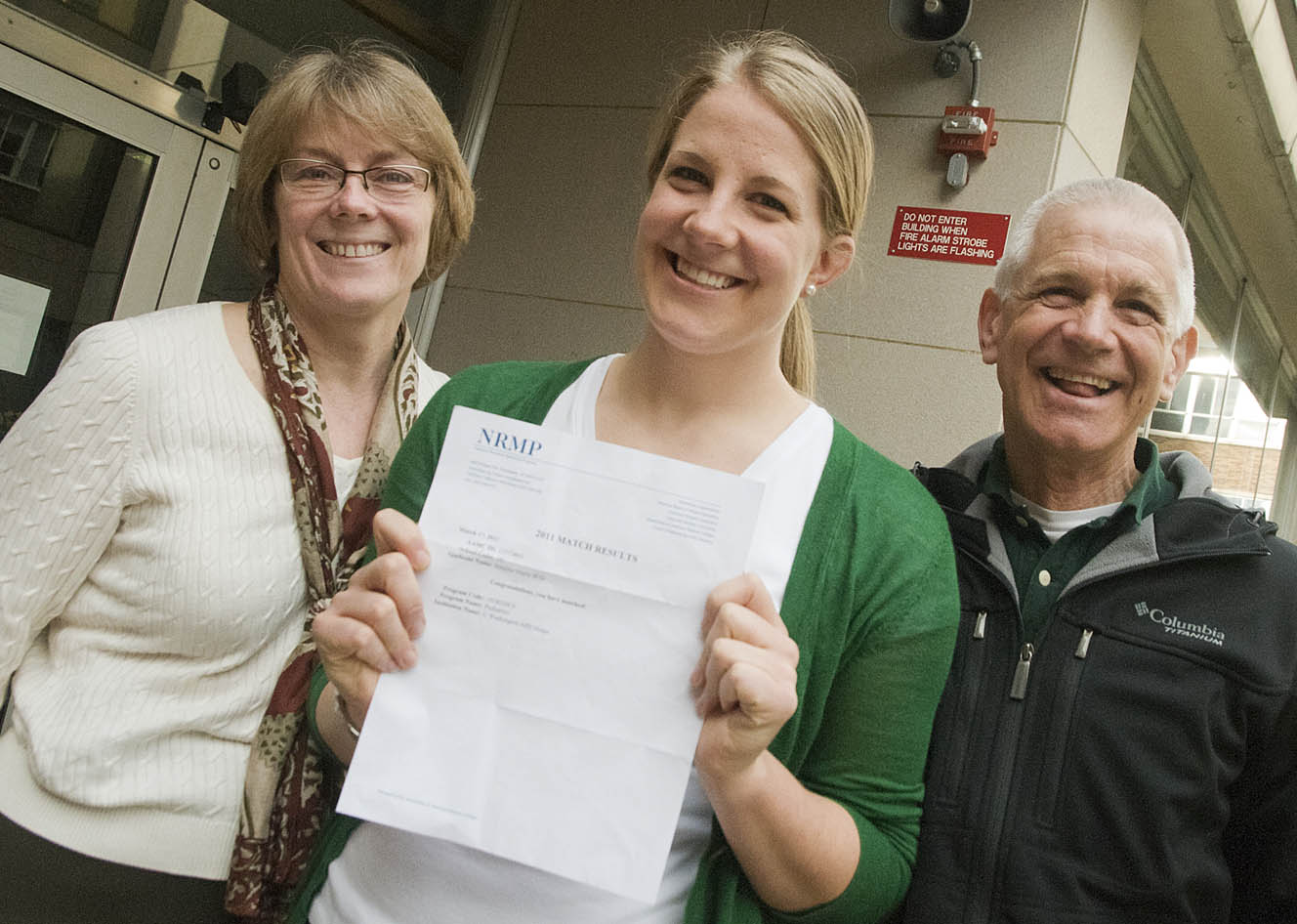 Jennie Wild, with parents and longtime UW employees Lorie and Silas Wild, holds up her residency placement letter.