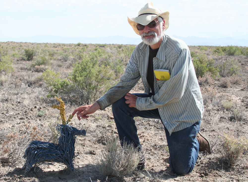 In central Utah, Donald Grayson kneels next to a woven model of the western North American diminutive pronghorn, which became extinct about 11,000 years ago.