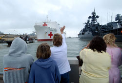 Friends and family members wave goodbye as a military hospital ship departs for a multi-month humanitarian assistance deployment.