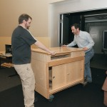 David Cornwall, left, and David Aldrich wheel in a cabinet which will house the hardware controlling classroom instructional systems.